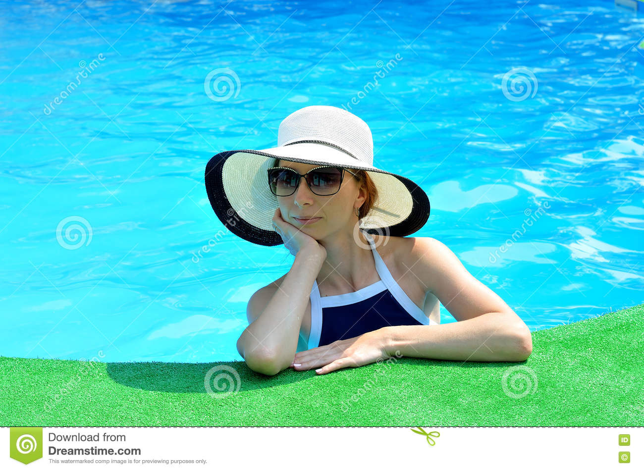 6f04a6cd Beautiful young woman in a sun hat and sunglasses on edge of pool, closeup  photo. woman with a hat relaxing at the pool.