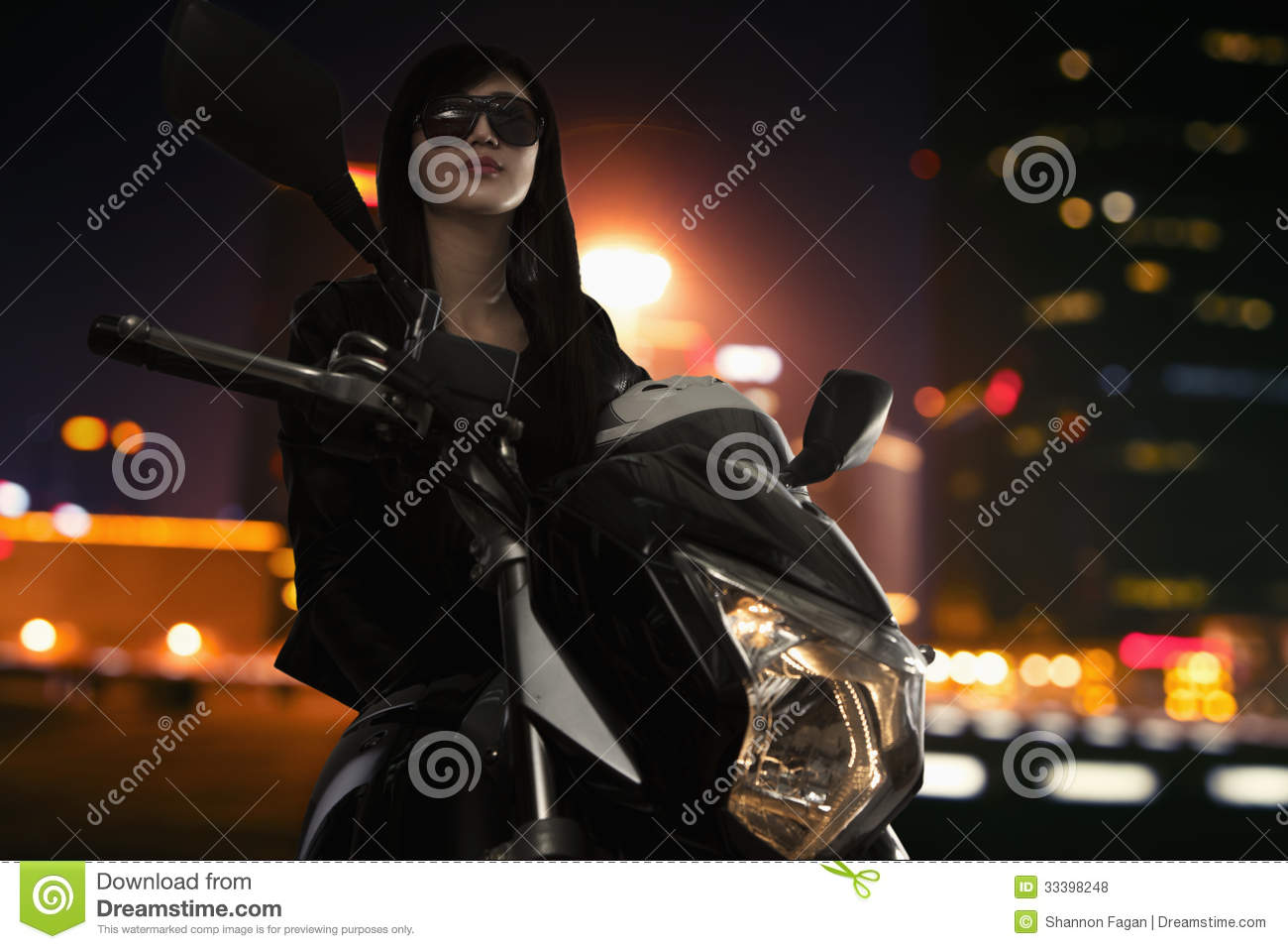 Beautiful young woman in sunglasses sitting on a motorcycle at night time in Beijing