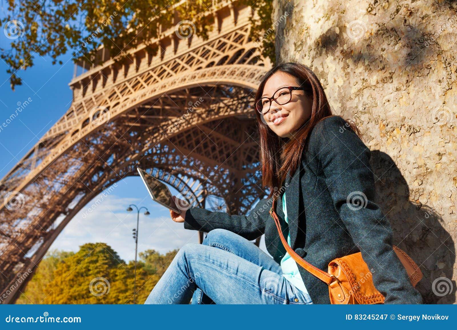 Beautiful young woman taking photo of Eiffel Tower
