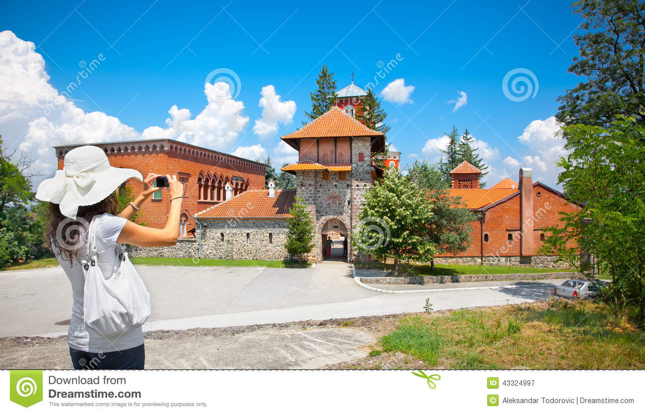 Beautiful young woman taking picture of Monastery Zica, Serbia.