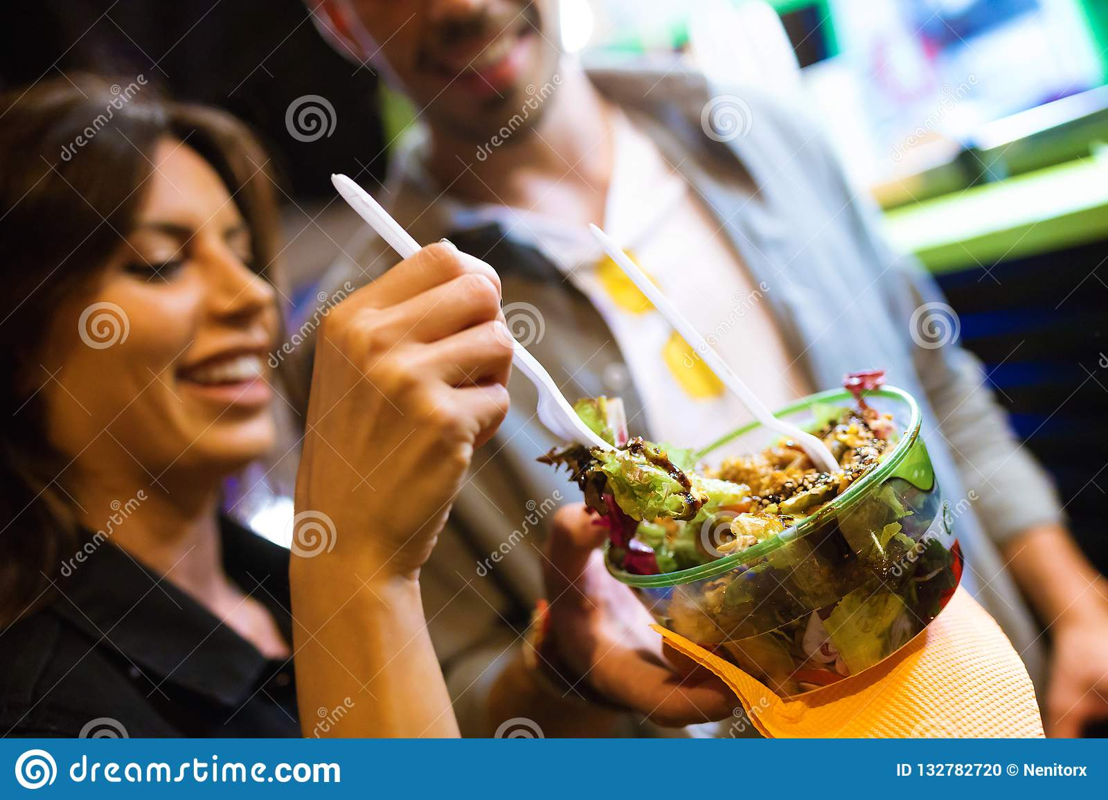 Beautiful young woman visiting eat market and eating colorful salad in the street.