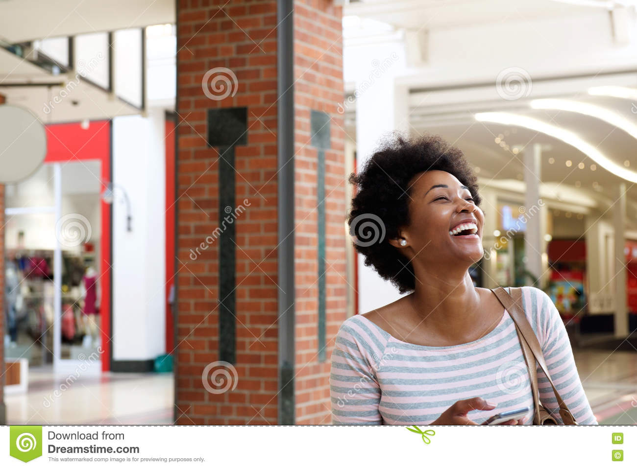 Beautiful young woman walking in mall with mobile phone