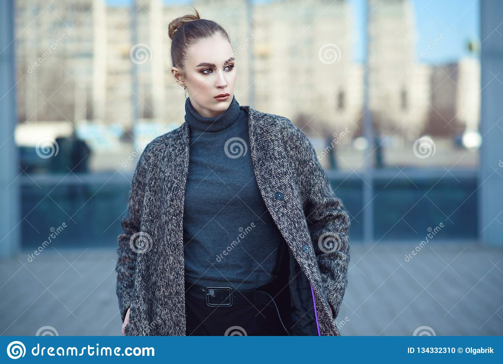 Beautiful young woman walking at the mirrored window of city mall