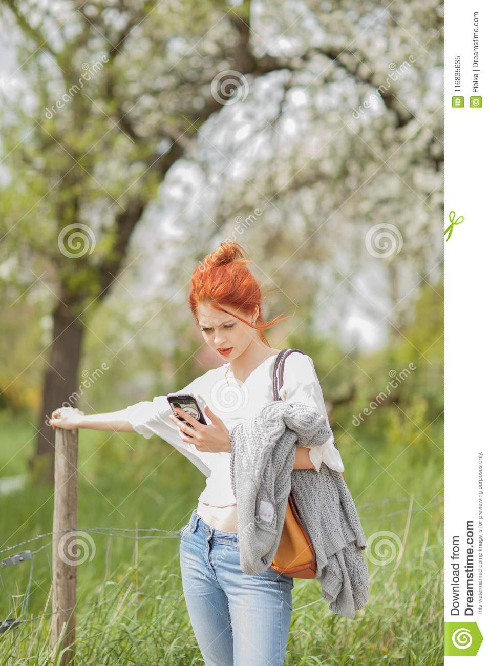 Beautiful young woman walking outside in a field, looking at her cell phone