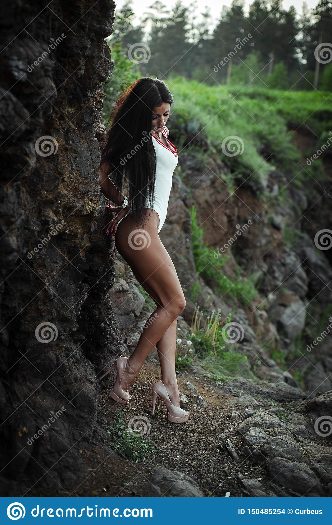 Beautiful young woman in white bodysuit with heels posing on stone background. Outdoor. Green