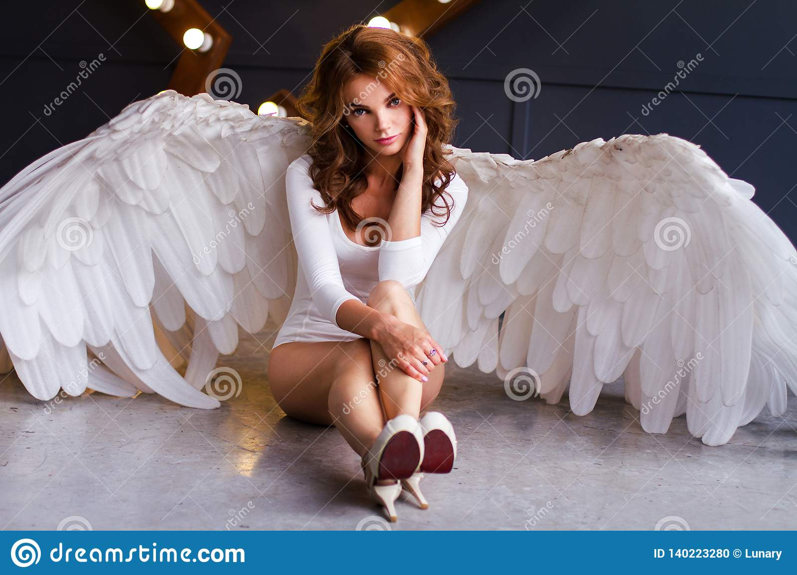 Young woman in white bodysuit with angel wings