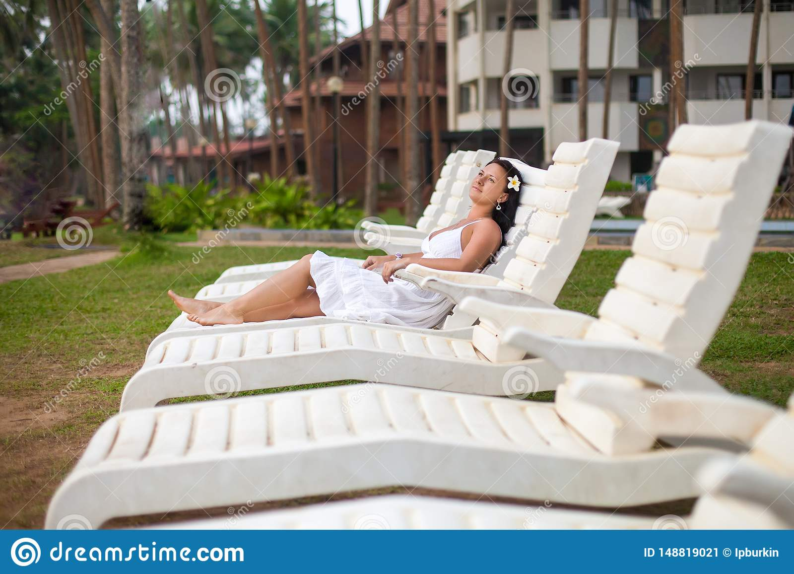 Beautiful young woman in white dress lying on a sun lounger by the sea. travel and Summer concept