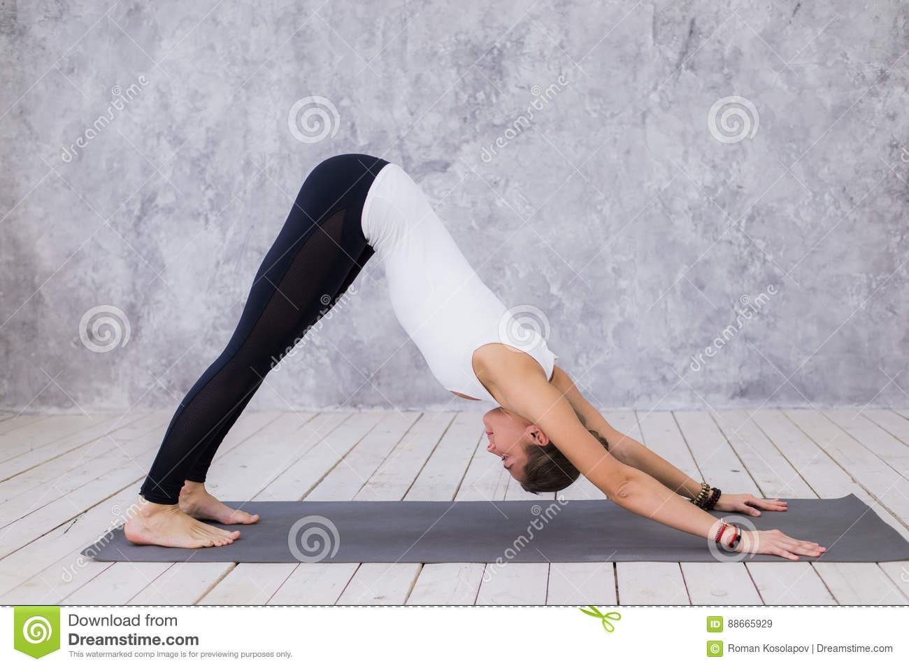 Beautiful young woman working out indoors, doing yoga exercise in the room with white walls, downward facing dog pose