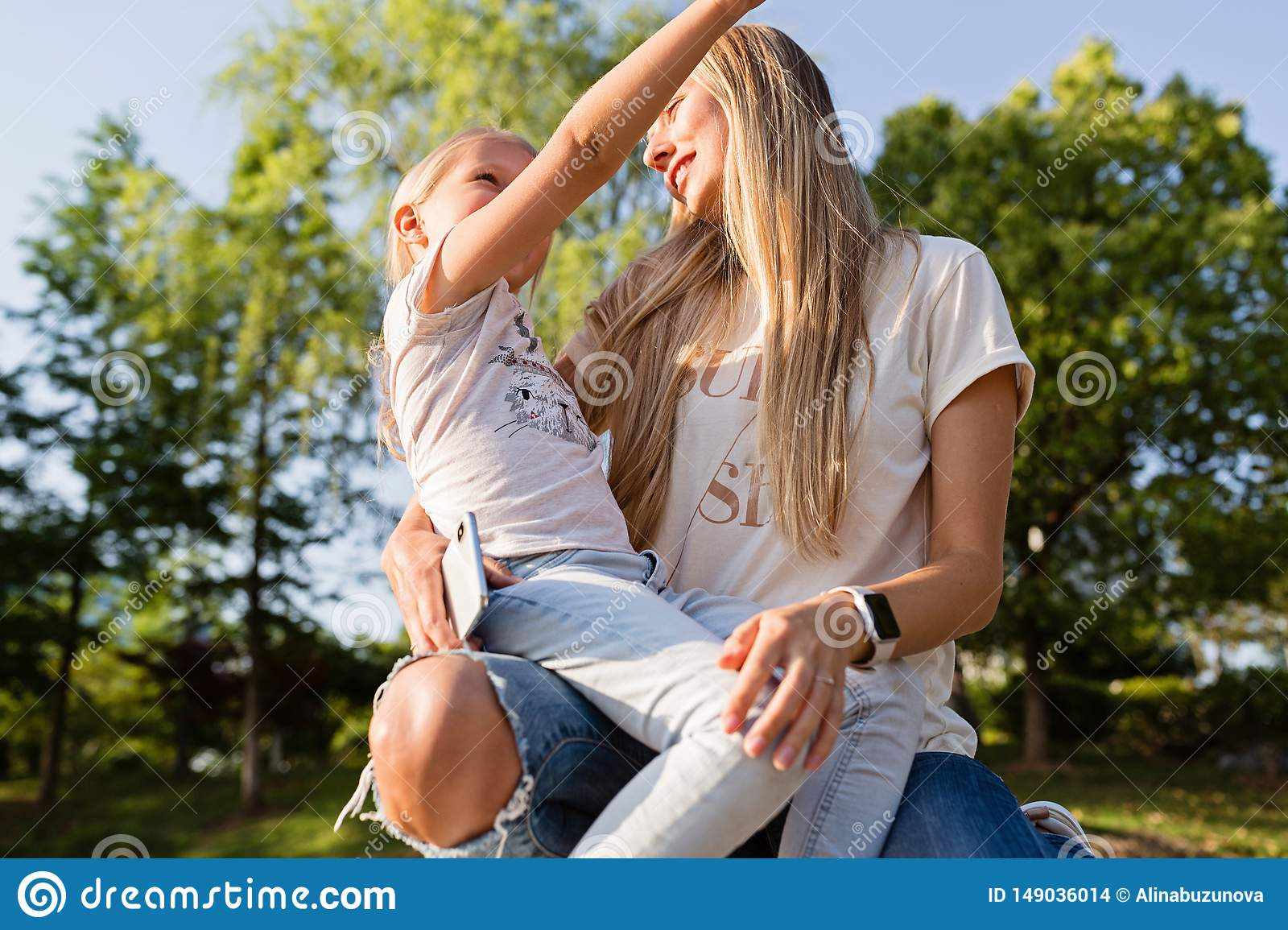 Beautiful young mother and daughter with blonde hair embracing outdoor. Stylish girls making walking in the park. Family concept