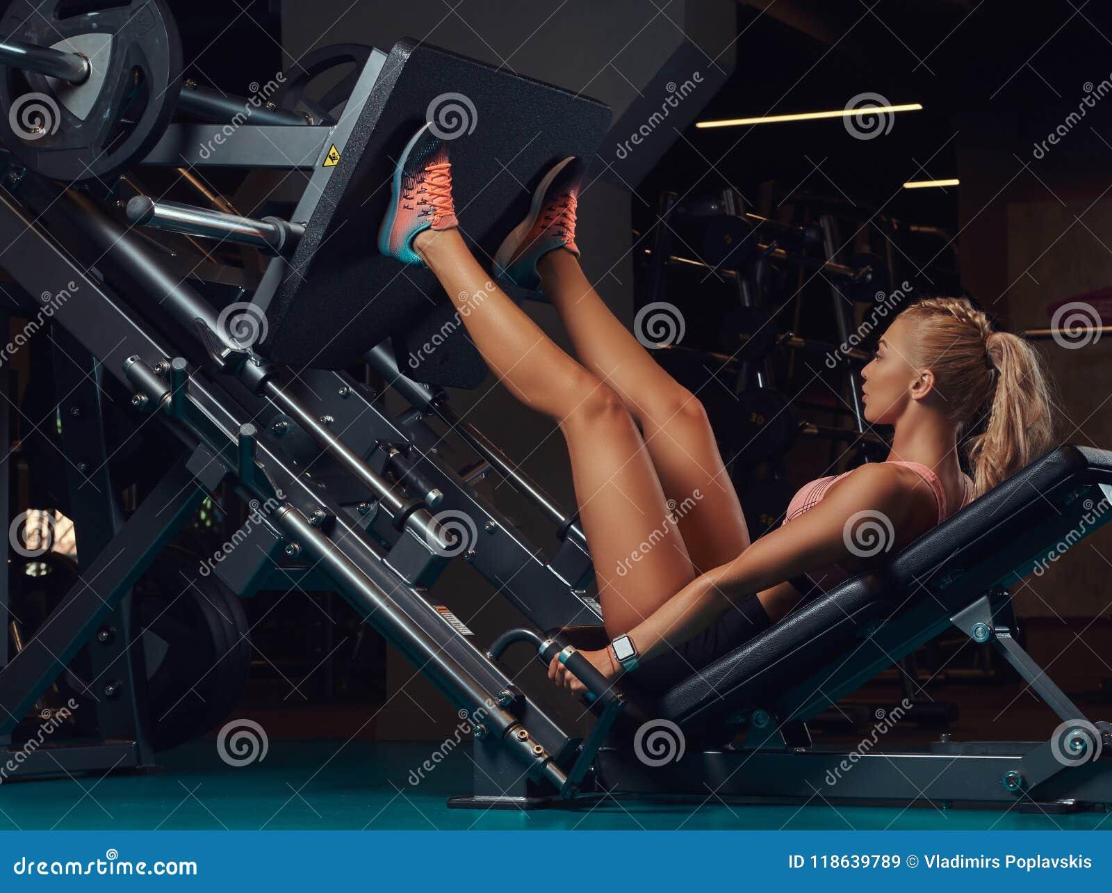 Beautifull做在腿的运动服的健身妇女锻炼按在健身房的机器