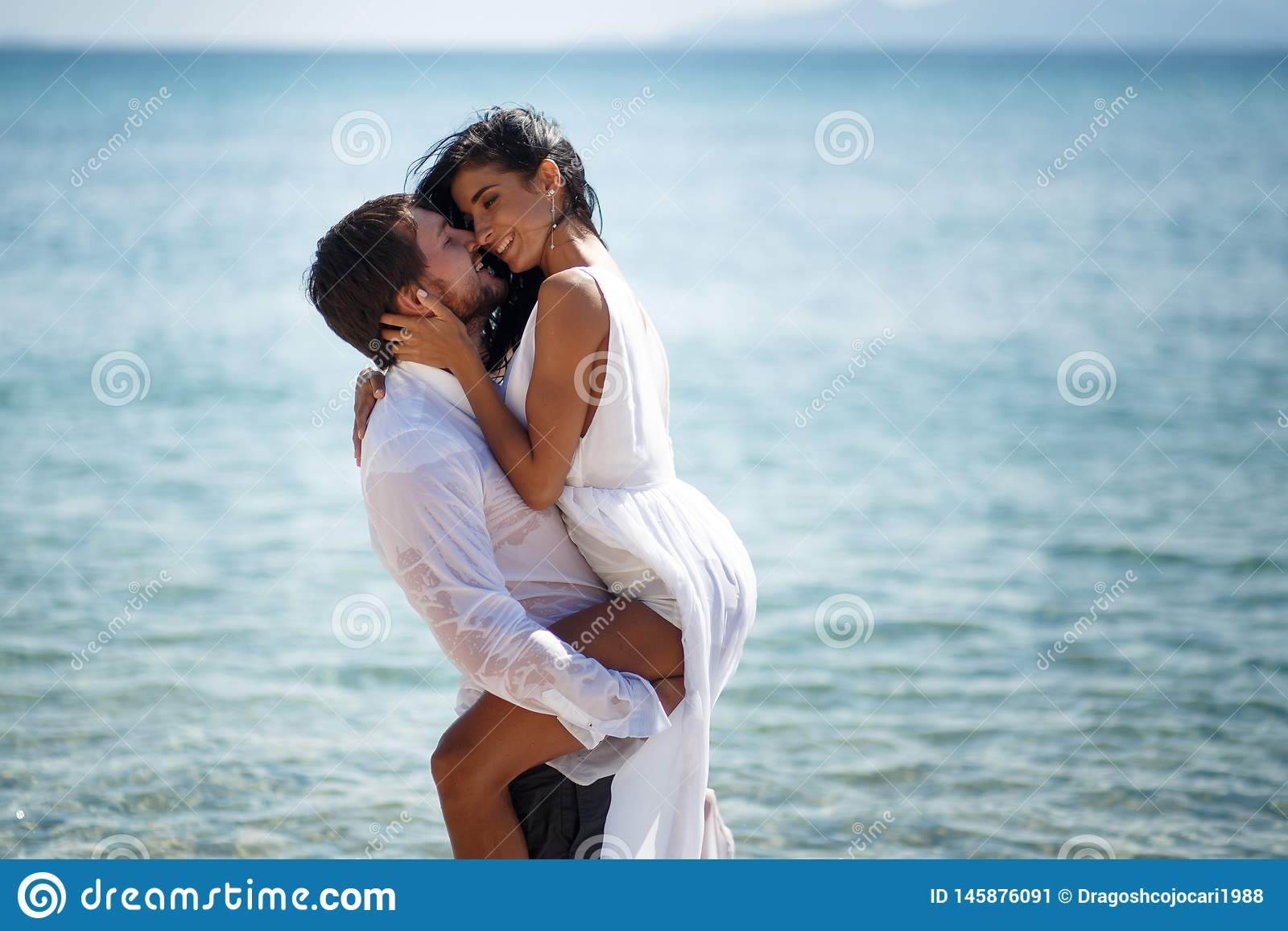 Beautiful wedding couple kissing and embracing in turquoise water, mediterranean sea in Greece.