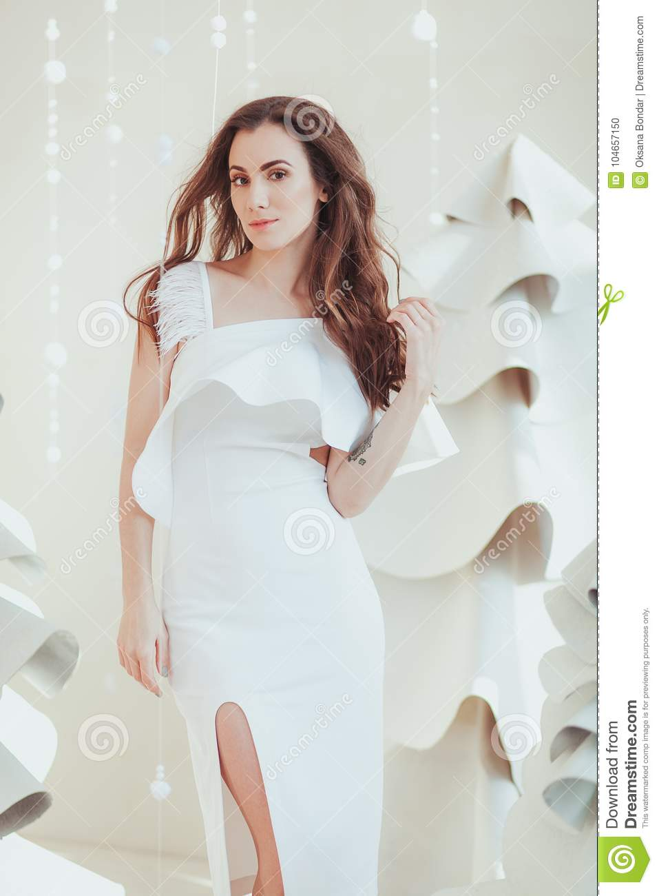 Beautifull young woman in white dress posing in fishion design studio room. Fabric christmas tree on background