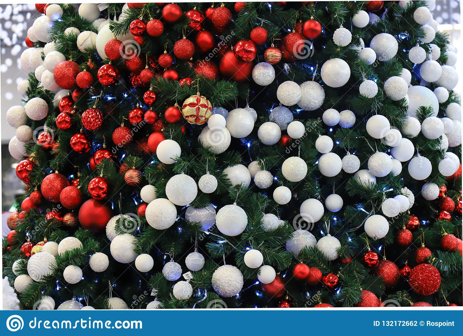 A beautifully decorated Christmas tree with red, white balls and garlands. Design and scenery, New Year s concept, winter holiday