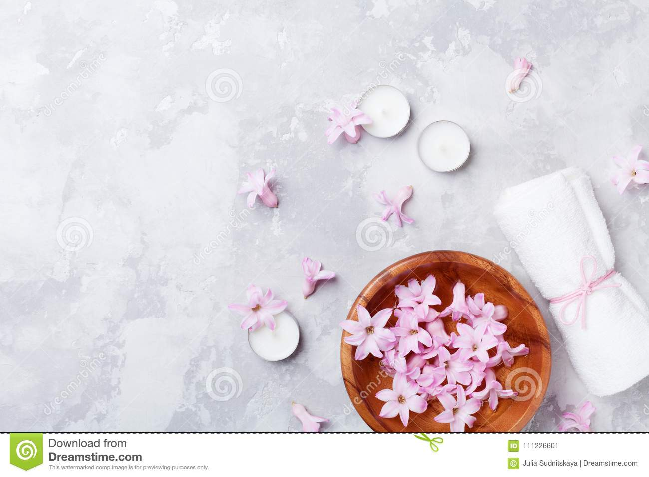 Beauty, aromatherapy and spa background with perfumed pink flowers water in wooden bowl and candles on stone table. Flat lay.