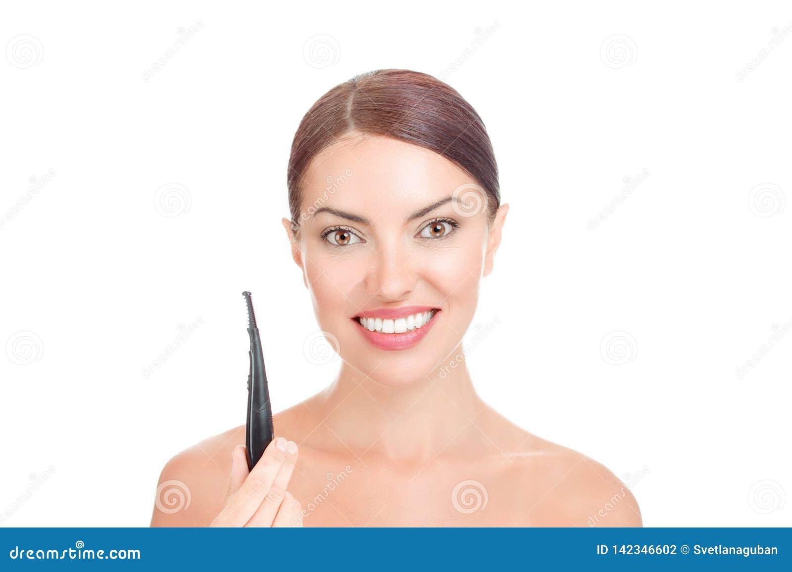 Beauty asian woman holding heated electric eyelash curler pen
