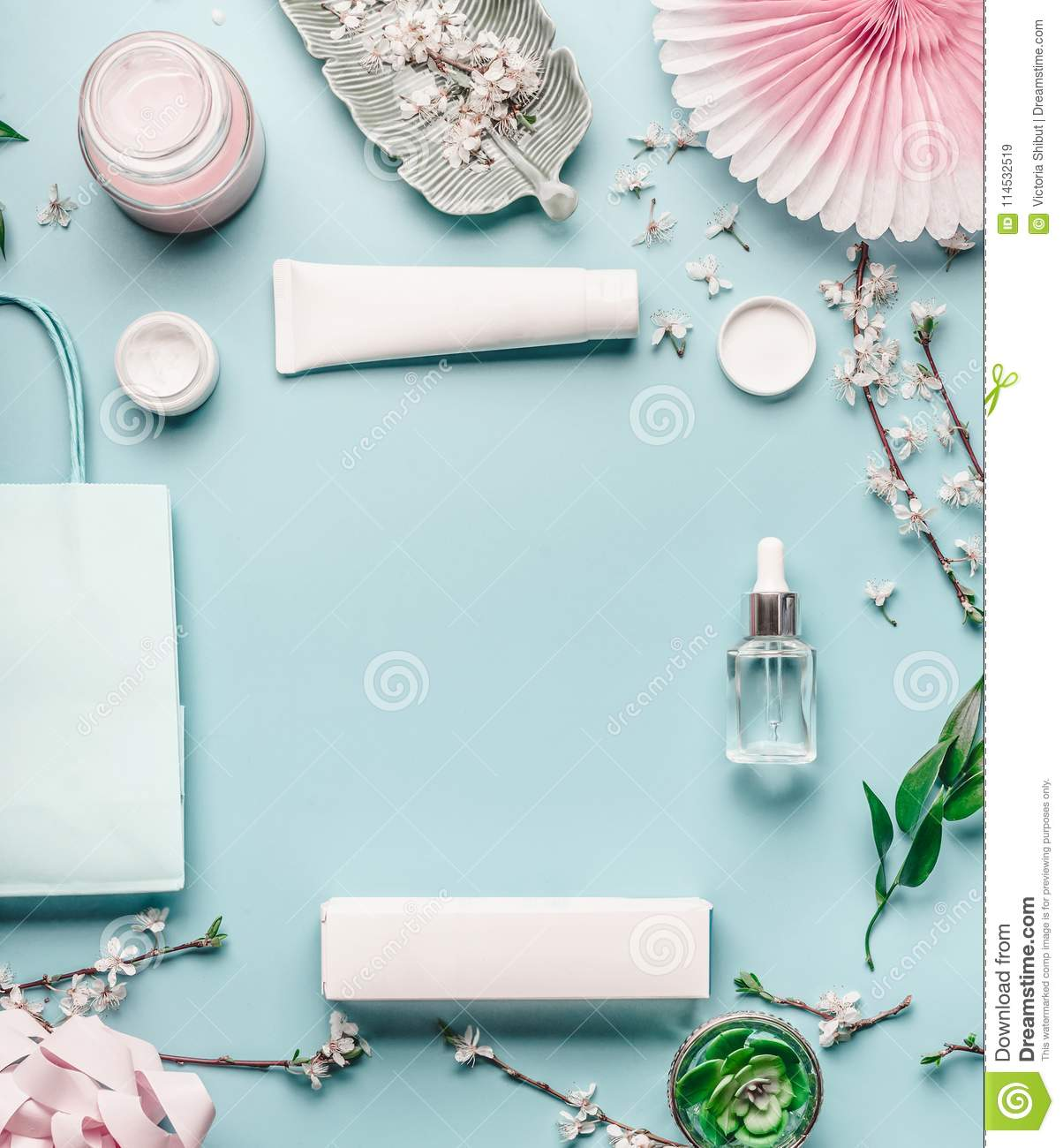 Beauty background with facial cosmetic products, shopping bag and twigs with cherry blossom on pastel blue desktop background.