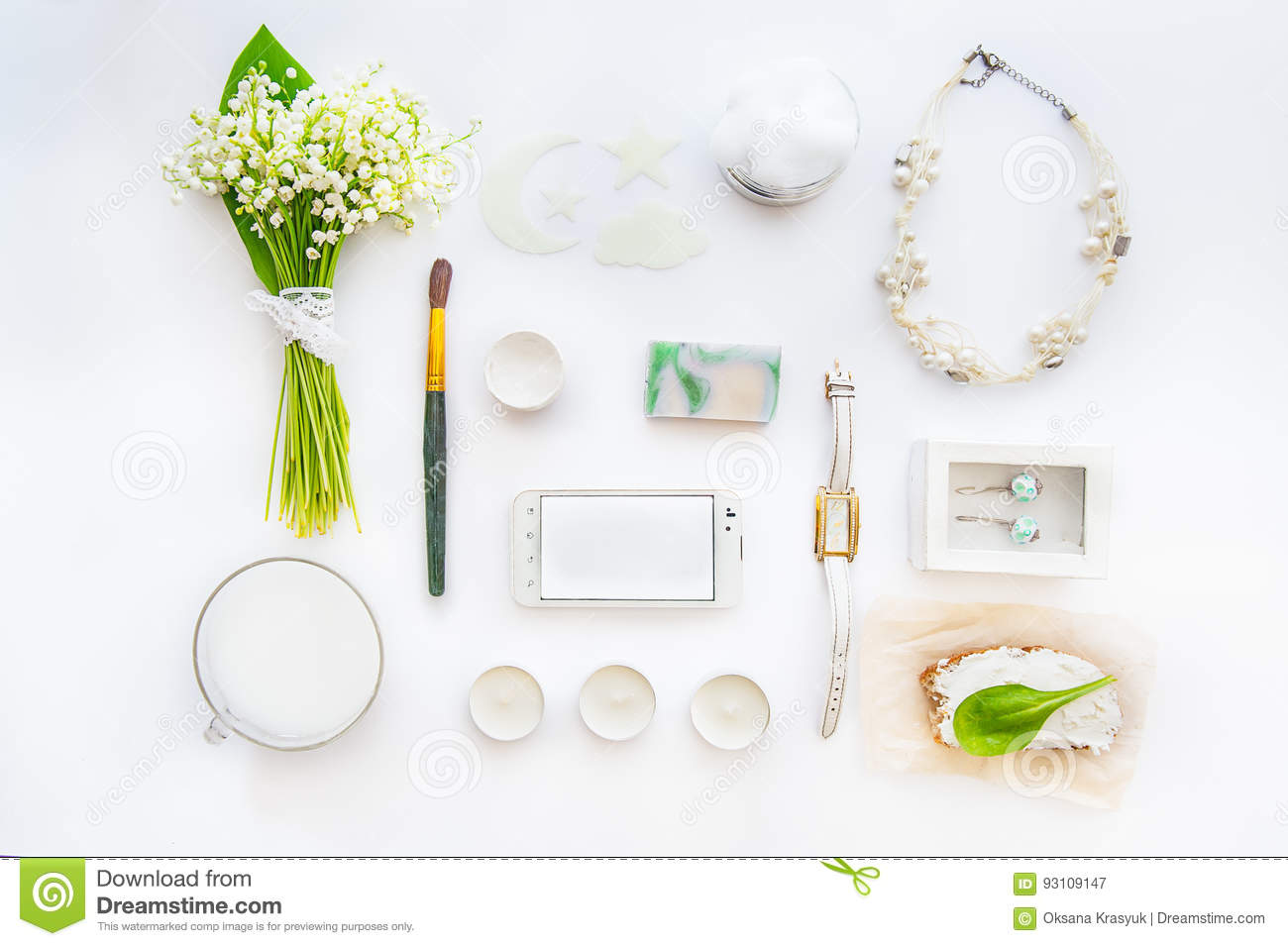 Beauty blog concept. Female styled accessories: smartfone, watches, necklace, cosmetic and bouquet of may-lily flowers on white ba