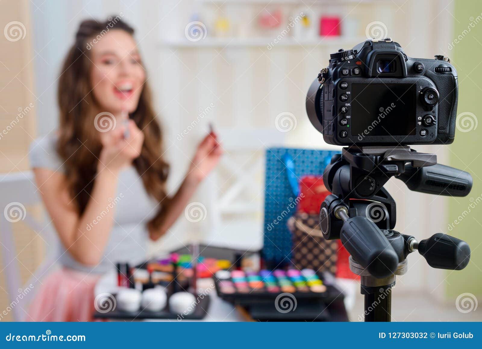 Beauty blogger applying lip gloss