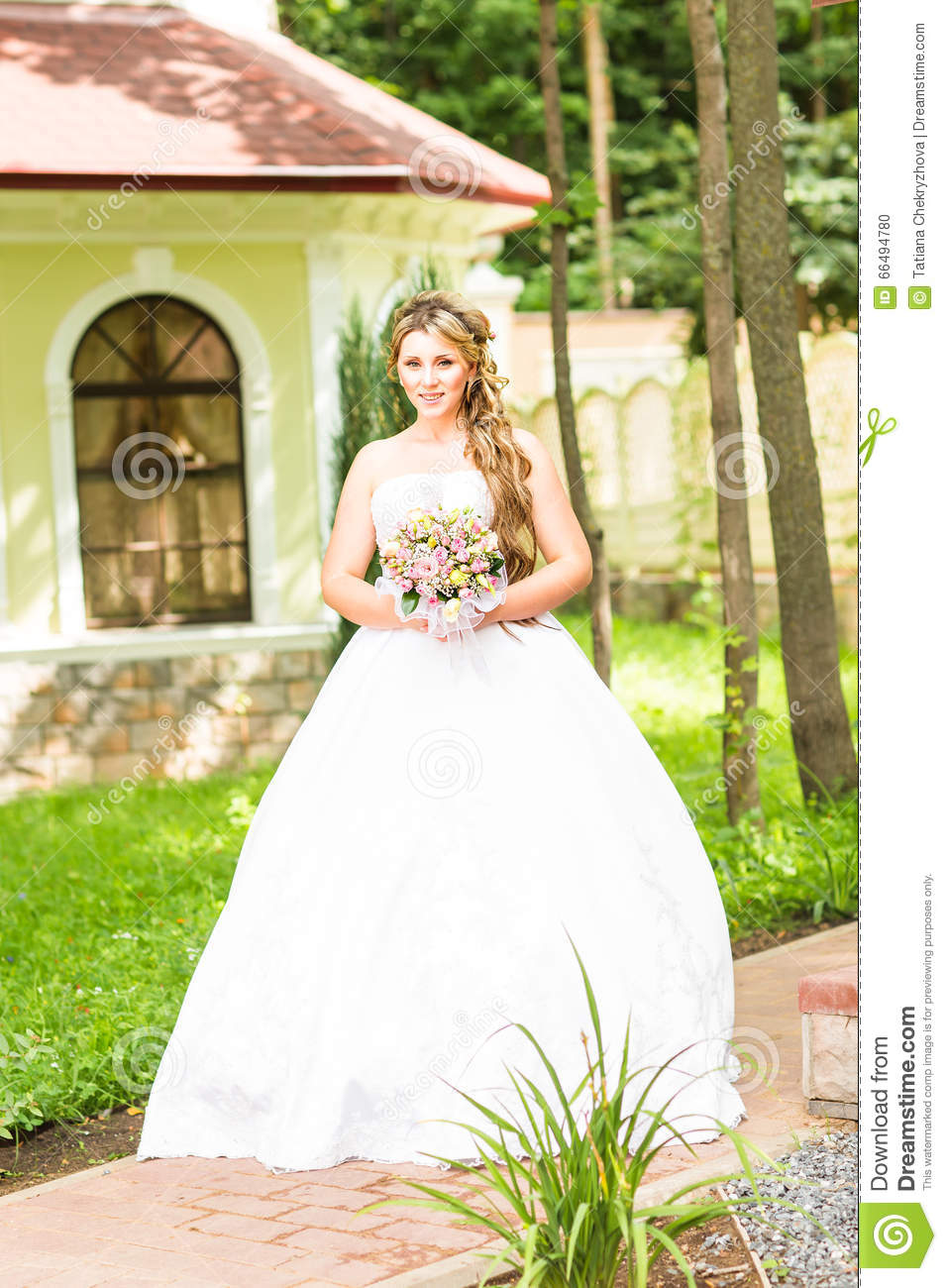 Beauty Bride In Bridal Gown With Bouquet And Lace Veil On The Nature ...