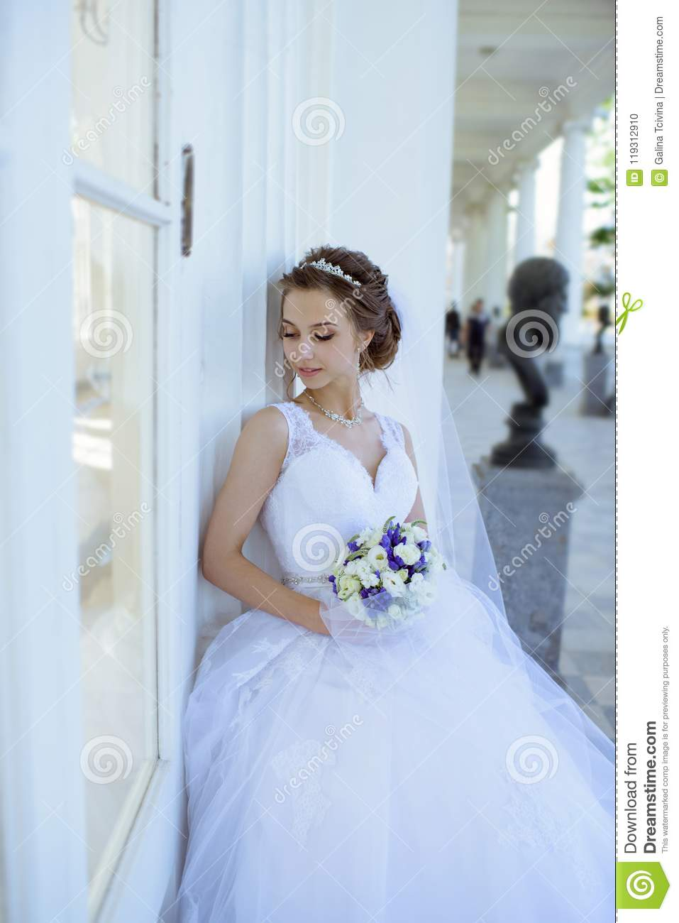 Beauty Bride In Bridal Gown With Bouquet And Lace Veil In The