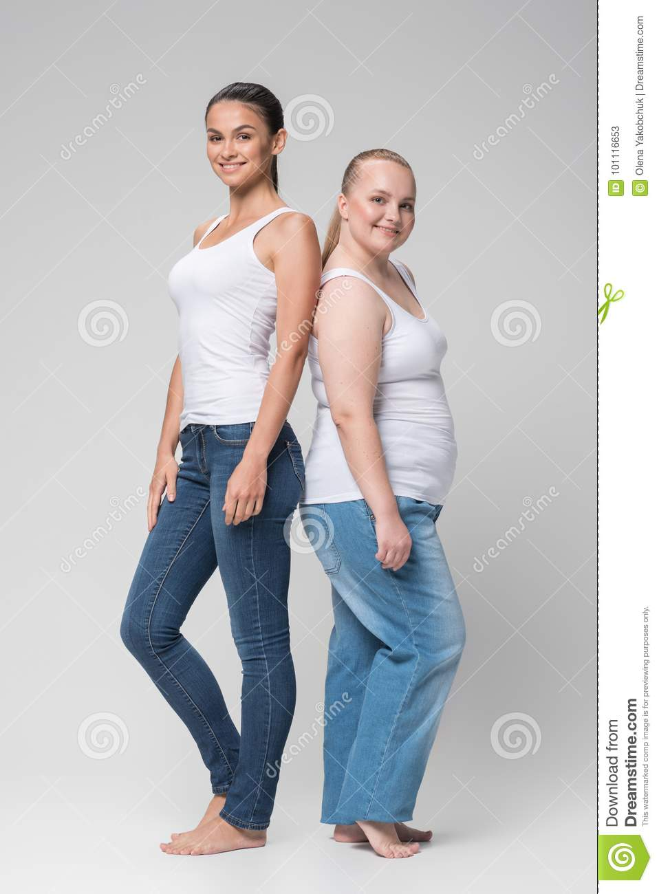 Full length portrait of happy young slim and fat women standing and  smiling. Isolated