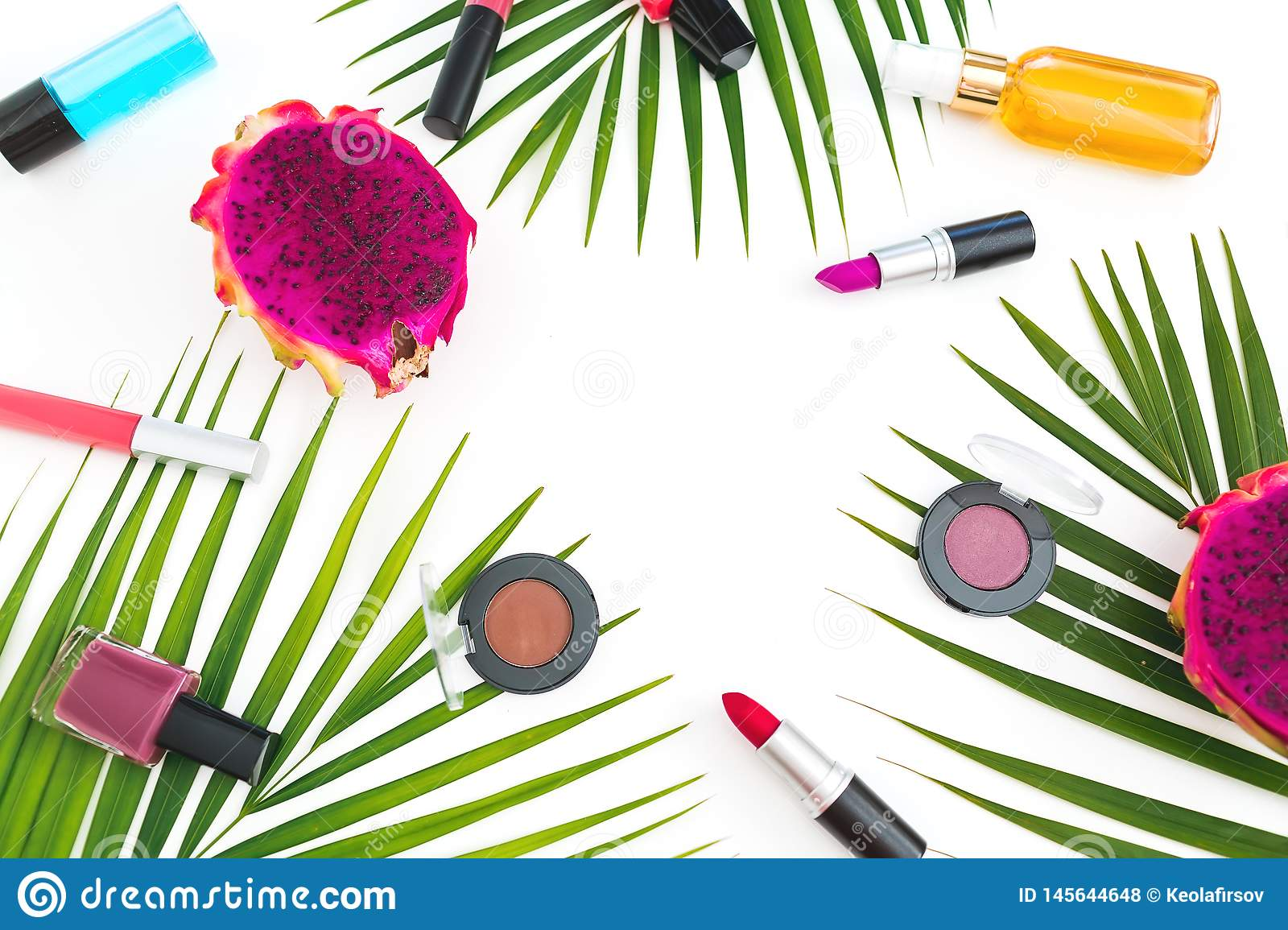 Beauty composition with dragon fruits, palm leaves and cosmetics on white background.