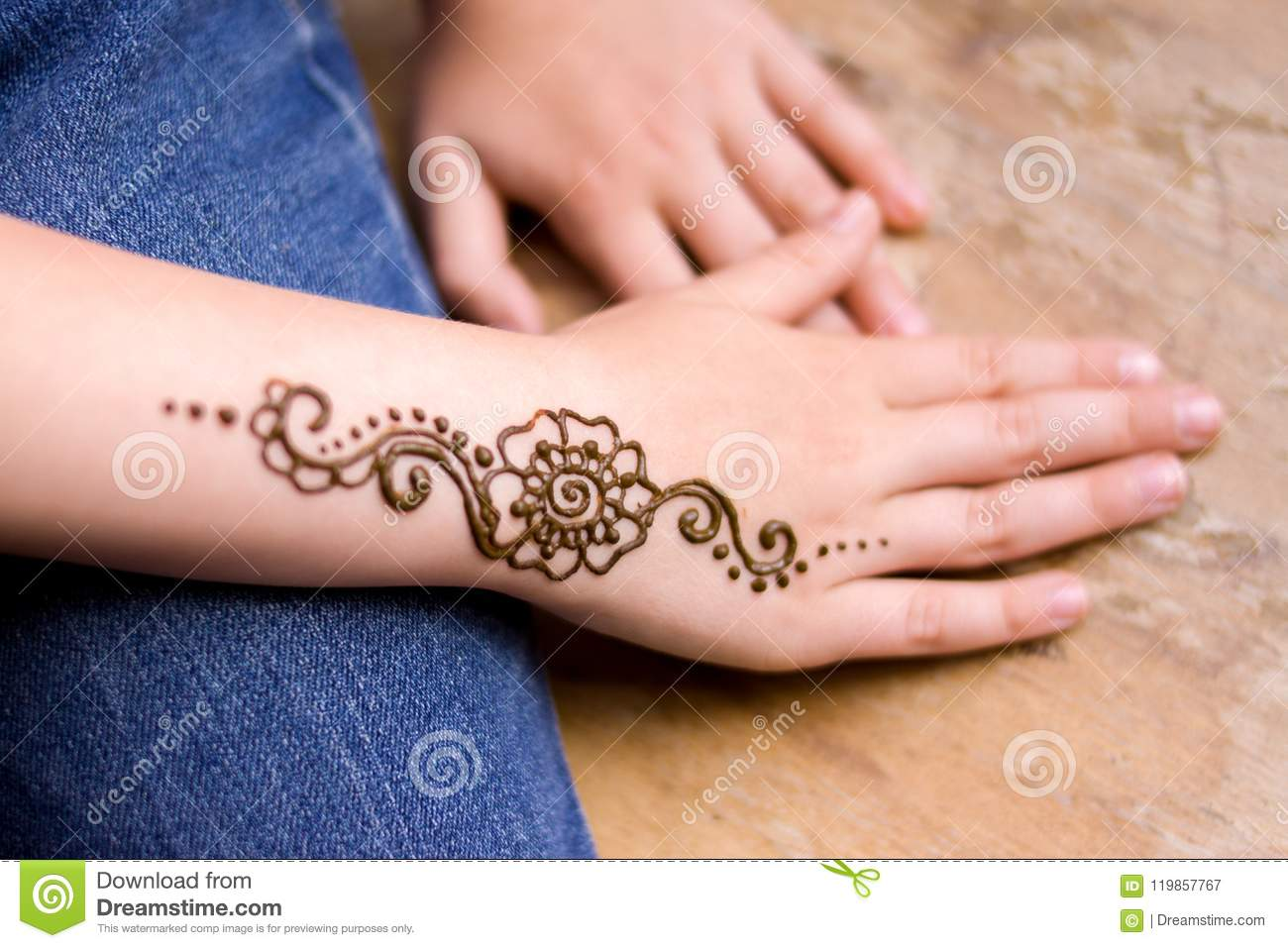 e77630d1e beauty concept - henna tattoo on small girl hand. Mehndi is traditional  Indian decorative art. Close-up, overhead view