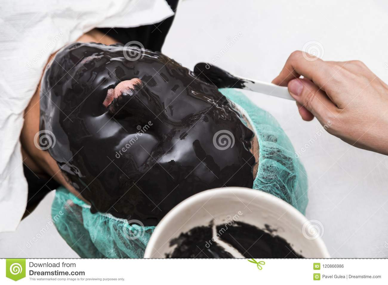 Beauty doctor apply skin alginate seaweed black mask to male patient face