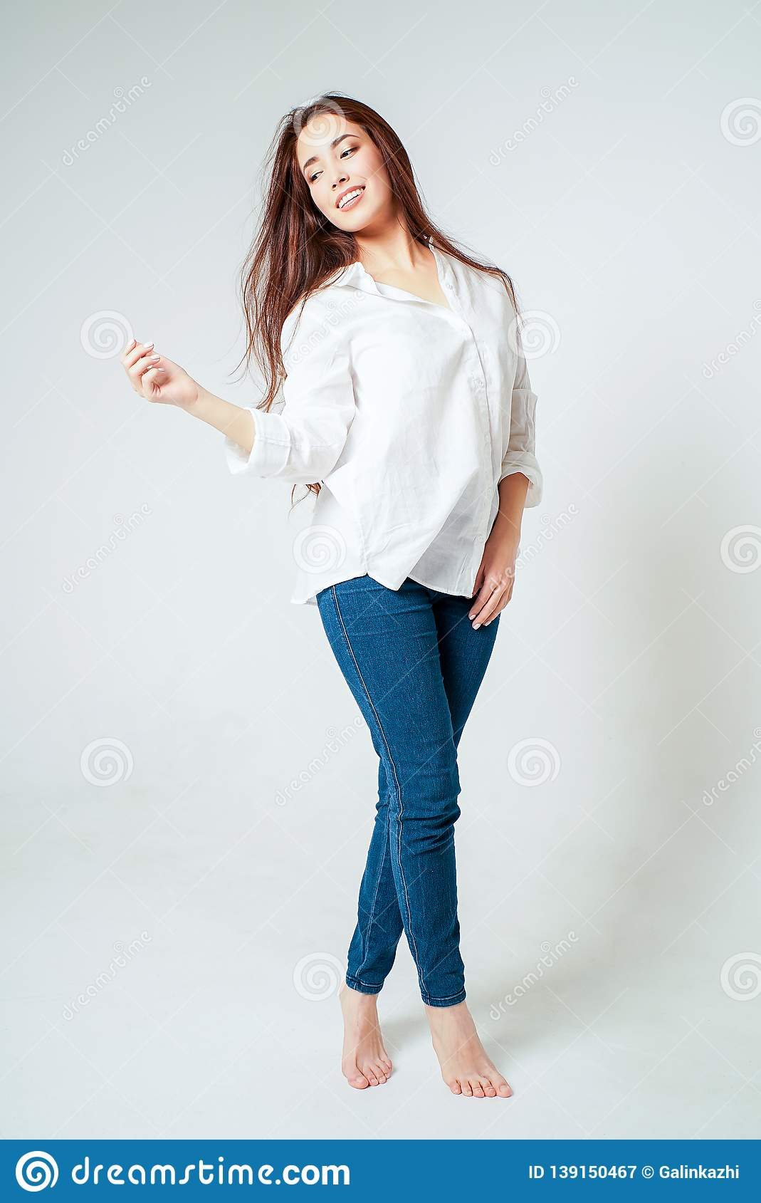Beauty fashion full length portrait of smiling sensual asian young woman with dark long hair in white shirt on white background