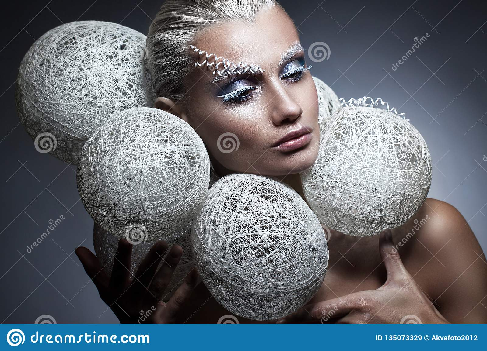 Beauty fashion portrait of a beautiful woman with creative makeup on her face. White braided balls around the head of the model