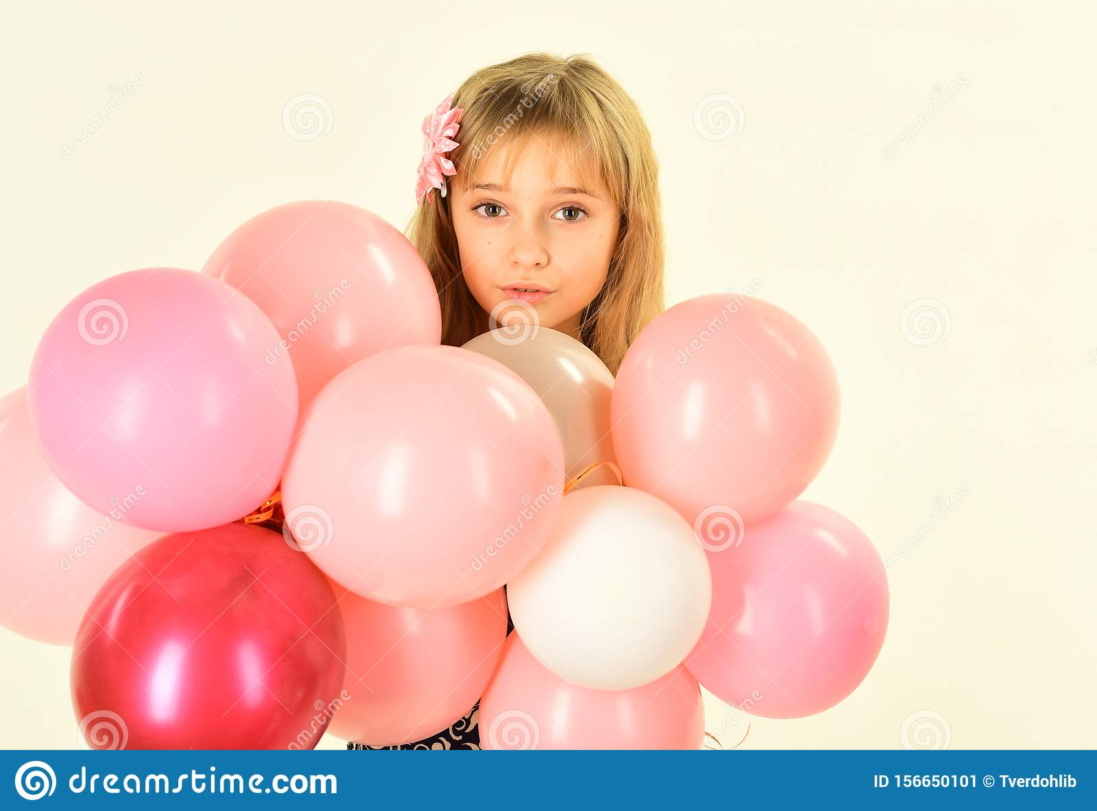 Beauty and fashion, punchy pastels. Little girl with hairstyle hold balloons. Small girl child with party balloons