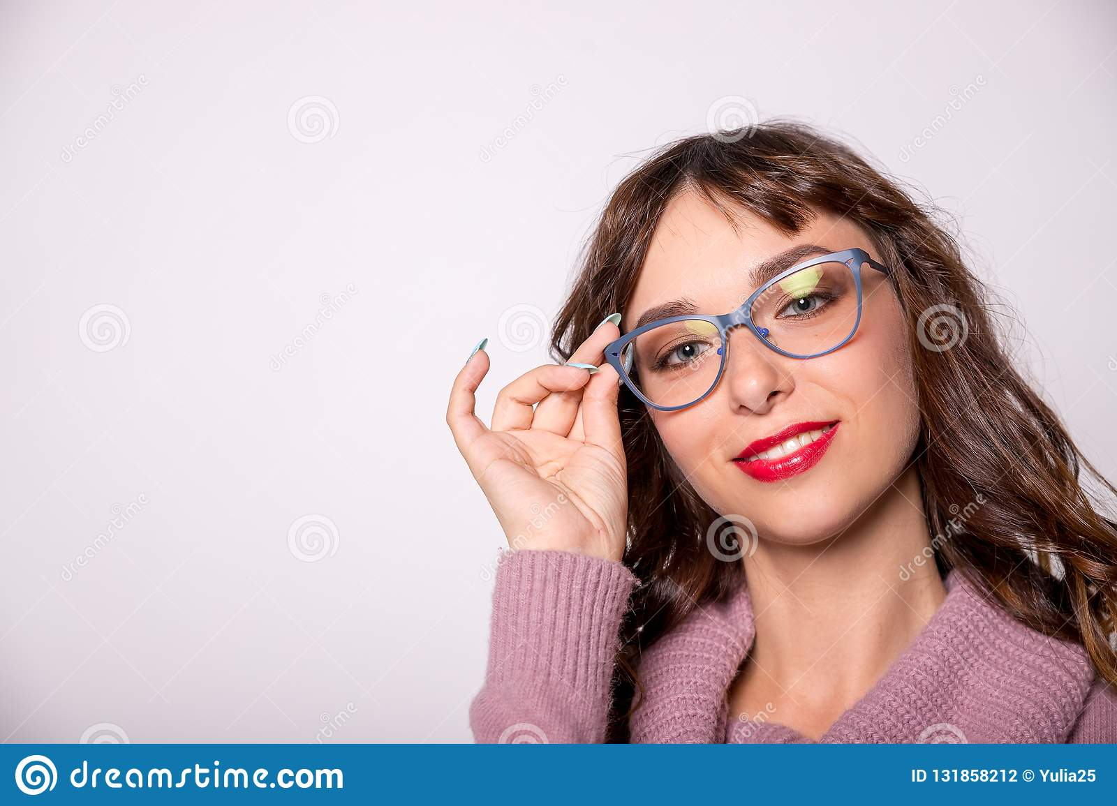 Beauty fashion girl wearing glasses showing empty copy space, white background. Happy girl presenting trendy