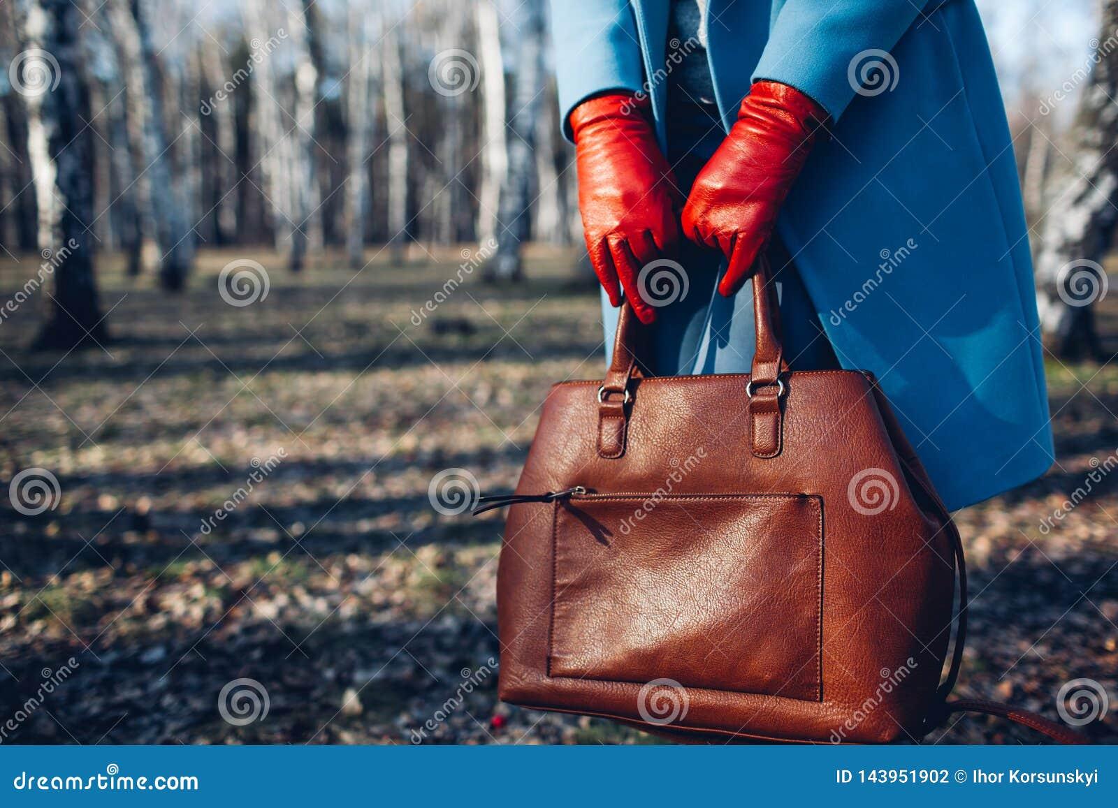 Beauty and fashion. Stylish fashionable woman wearing bright dress holding brown bag handbag