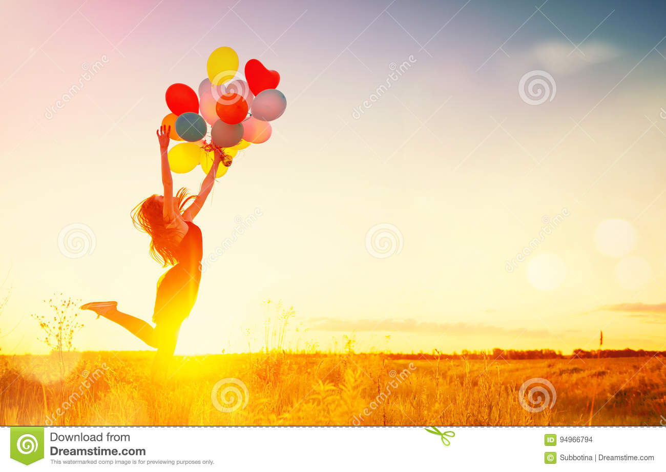 Beauty girl with colorful air balloons over sunset sky