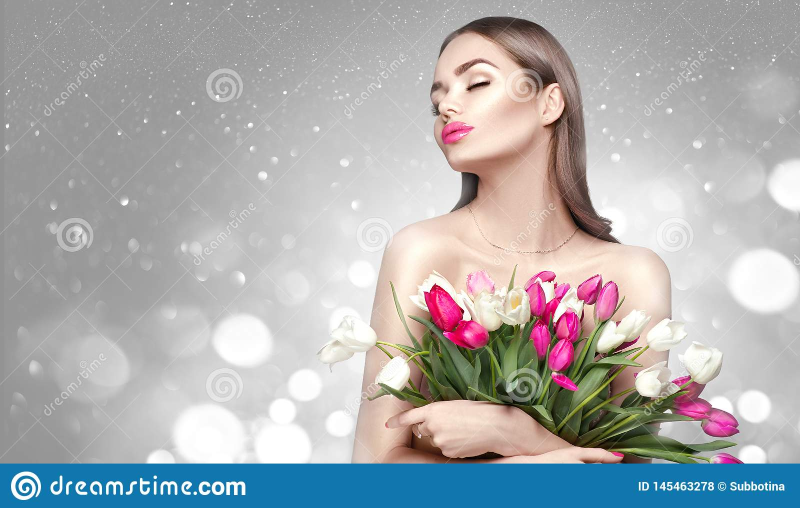 Beauty girl holding spring tulips. Beautiful woman receiving a bouquet of colorful tulips