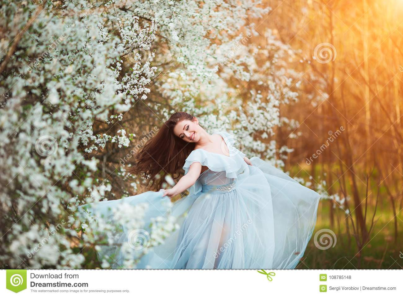 Happy beautiful young woman with long black healthy hair enjoy fresh  flowers and sun light in blossom park at sunset. fc8fe8b29