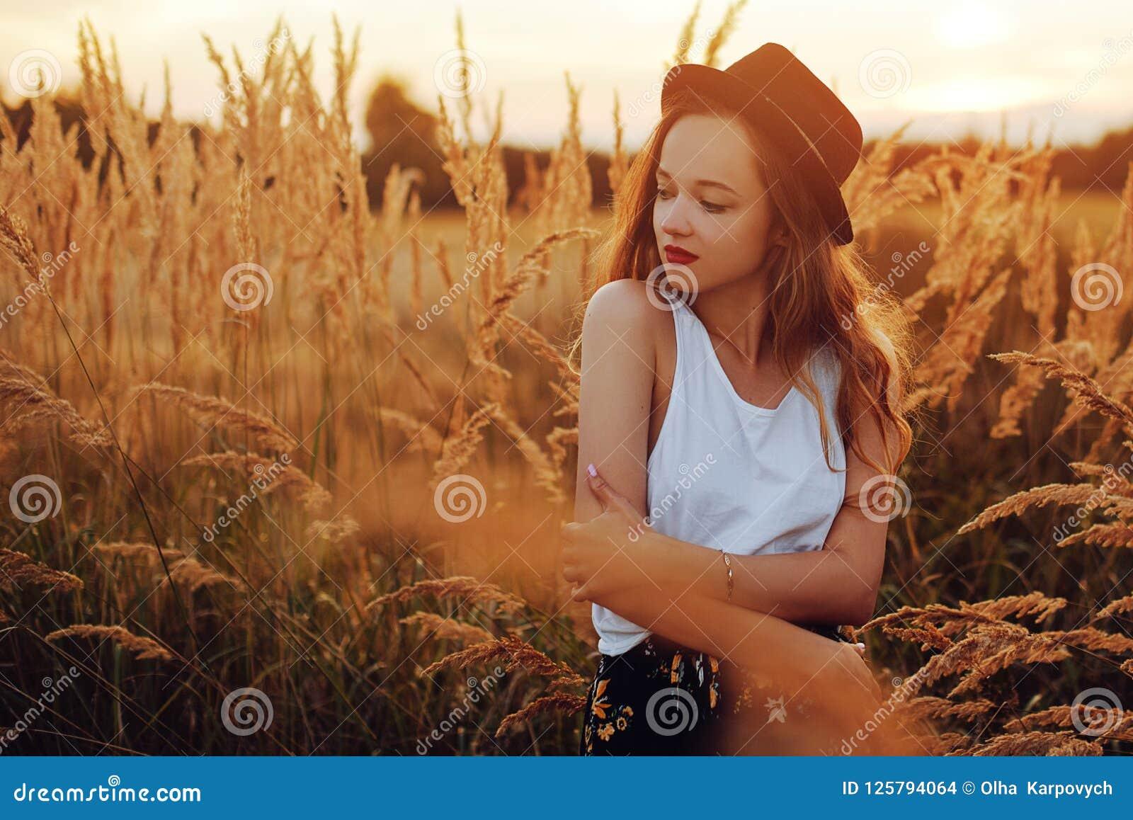 Beauty Girl Outdoors enjoying nature. Pretty Teenage Model in hat running on the Spring Field, Sun Light. Romantic