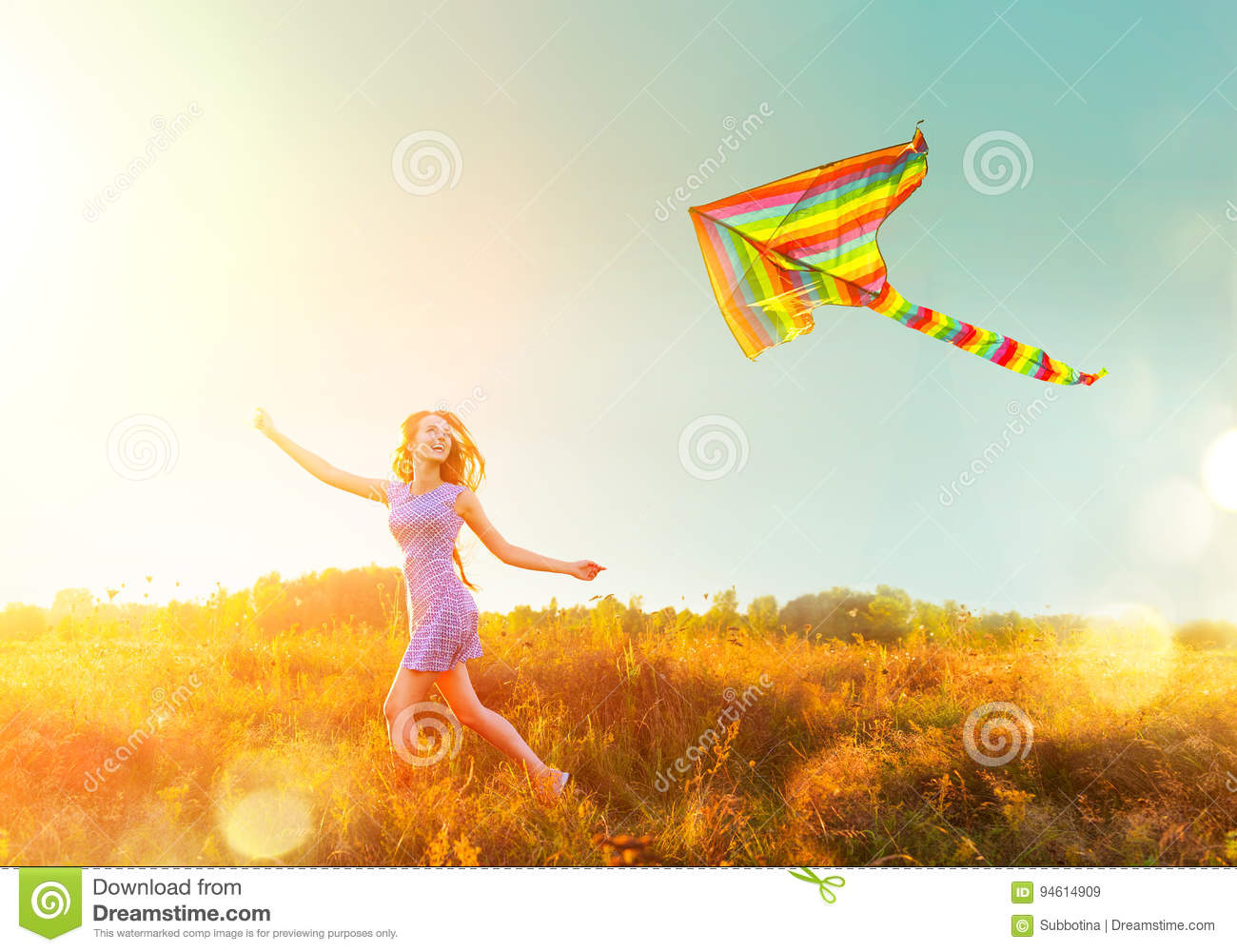 Beauty girl in short dress running with flying colorful kite
