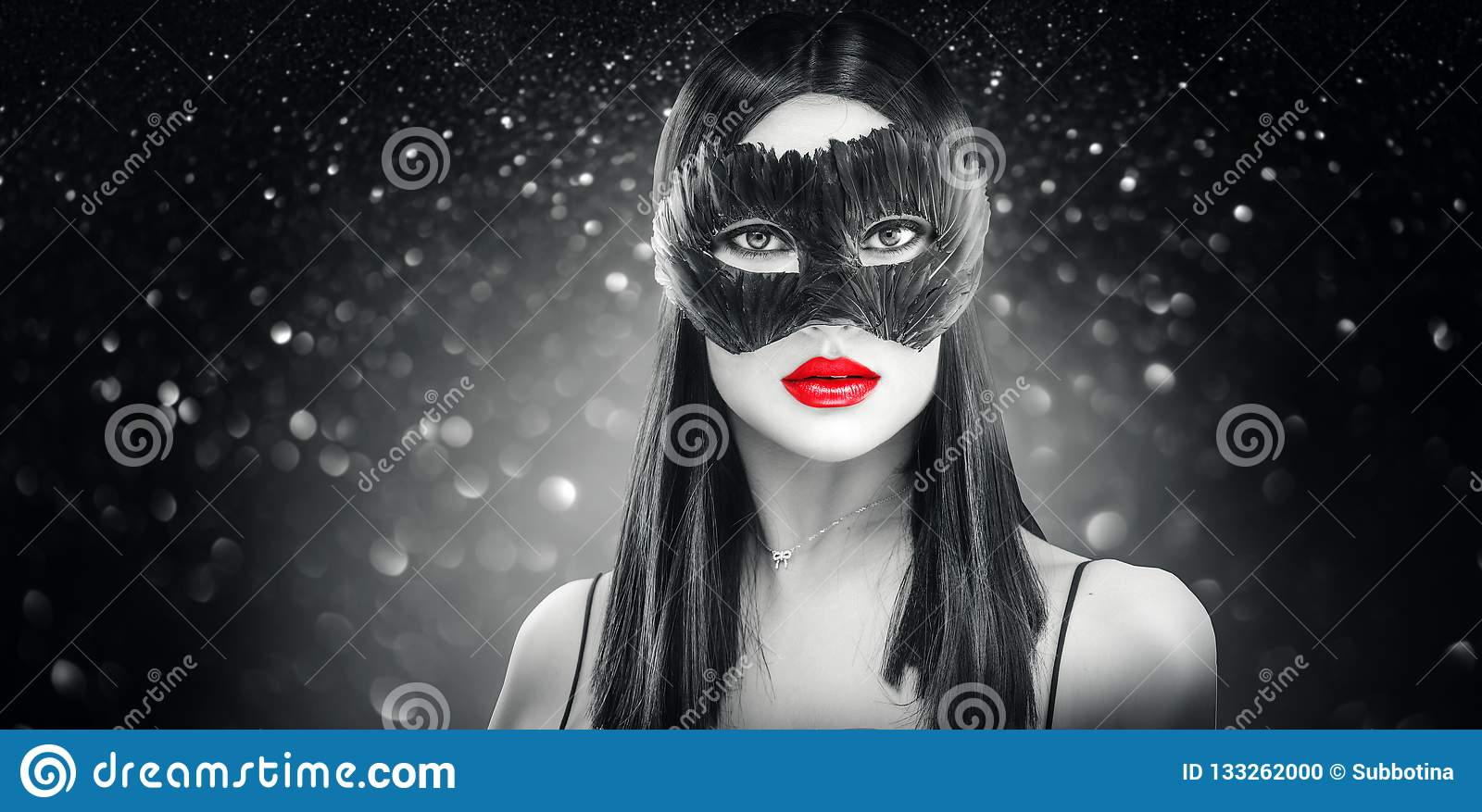 Beauty glamour brunette woman wearing carnival feather dark mask, party over holiday black background