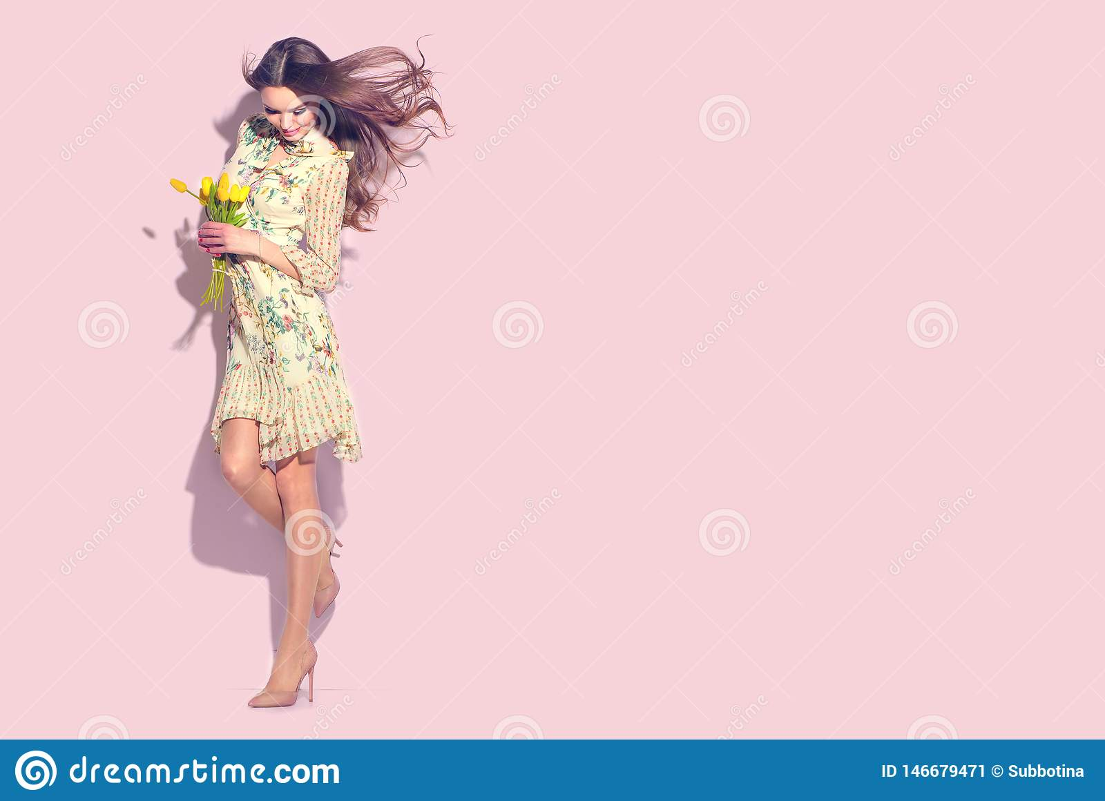 Beauty glamour girl with spring tulip flowers. Beautiful young woman posing with bouquet of tulips. Model wearing chiffon dress
