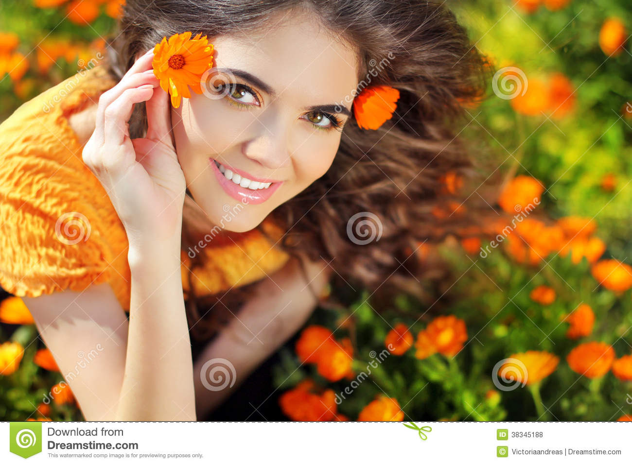 Beauty happy Romantic woman Outdoors. Beautiful Teenage girl embracing in golden marigold flowers