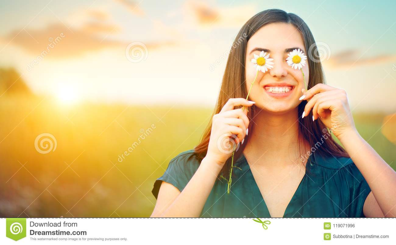Beauty joyful girl with daisy flowers on her eyes enjoying nature and laughing on summer field