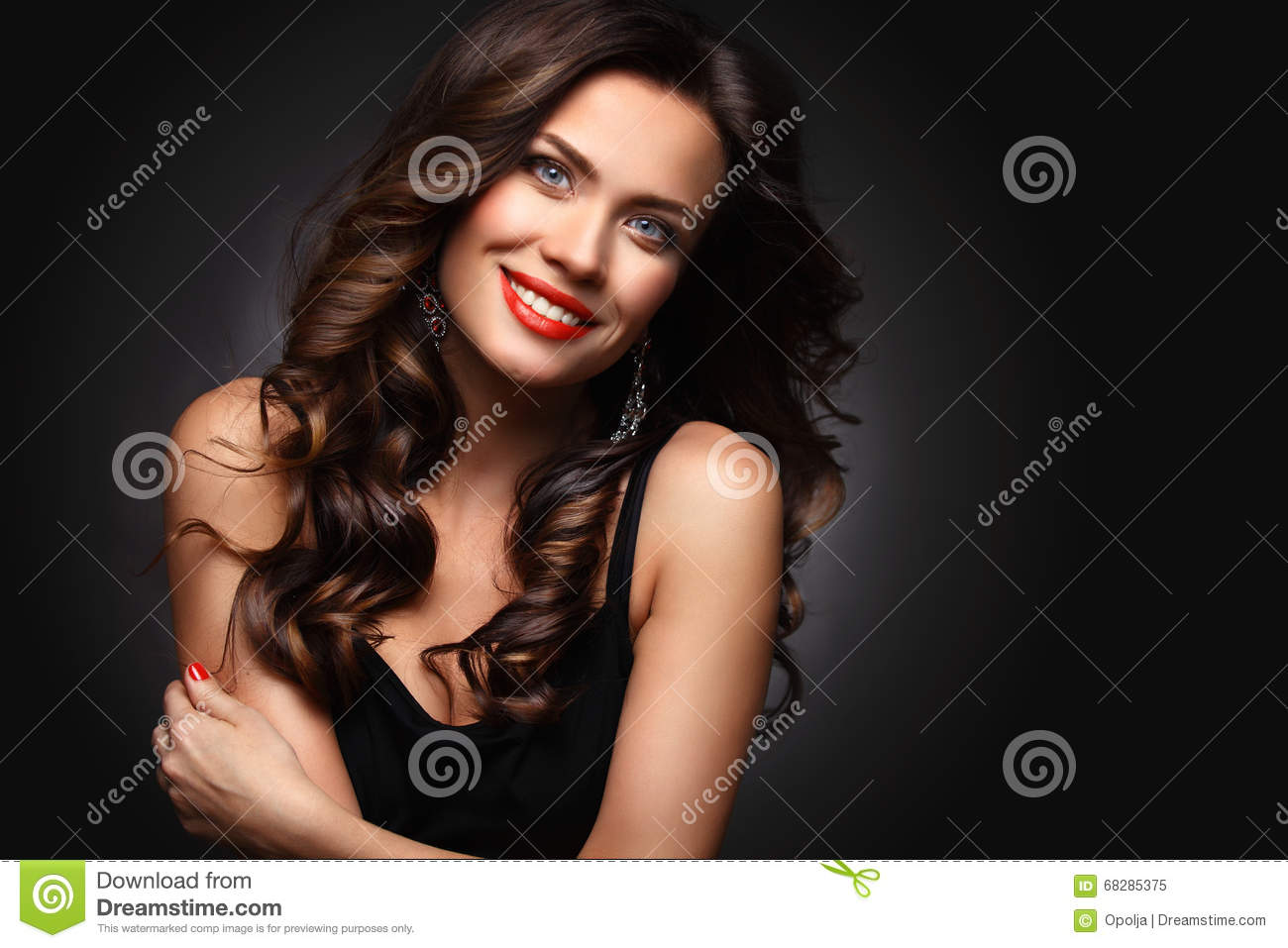 Beauty Model Woman with Long Brown Wavy Hair. Healthy Hair and Beautiful Professional Makeup. Red Lips and Smoky Eyes