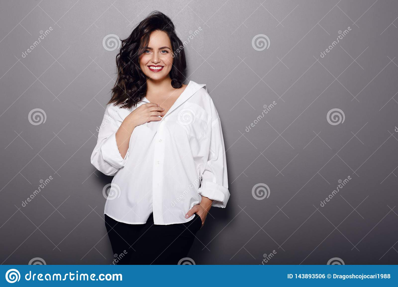 Beauty portrait of cheerful brunette woman, wear in white shirt and black pants, isolated on a grey background
