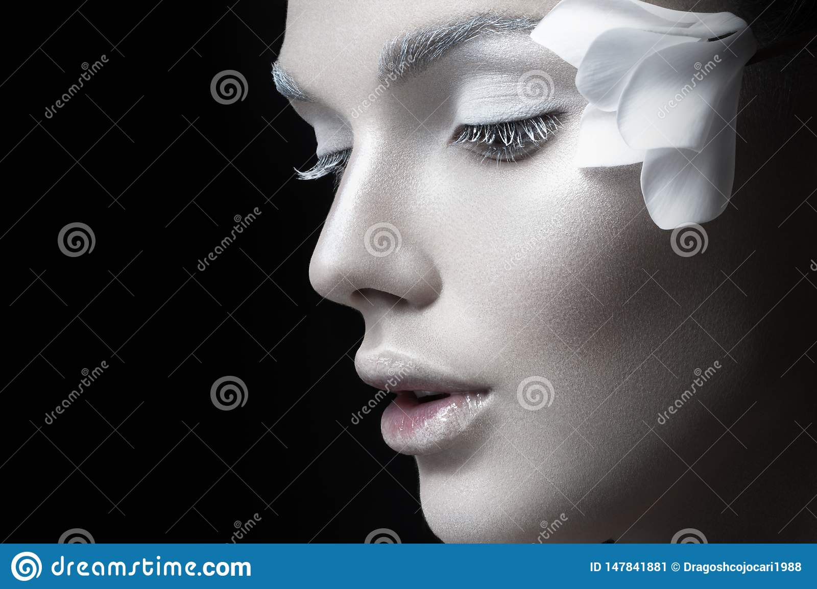 Beauty portrait., girl with white makeup, anf flowers near ear. Concept makeup, cosmetics,  on black background.