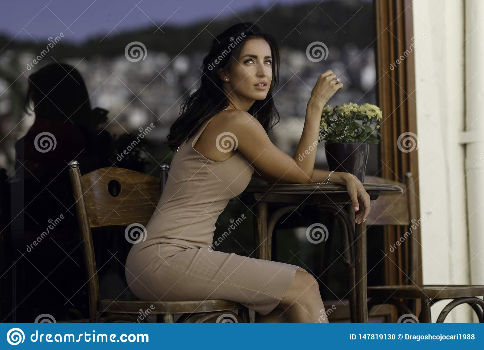 Profile beauty portrait of a graceful brunette young woman, stays at a coffee table, poses alone gorgeous outside.