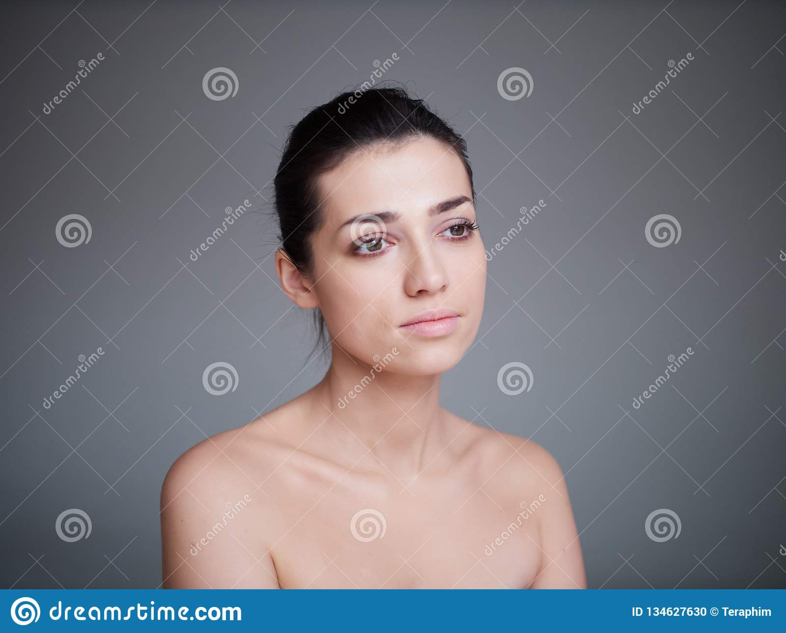 Beauty portrait of healthy female face with natural skin on grey background. Cosmetology concept