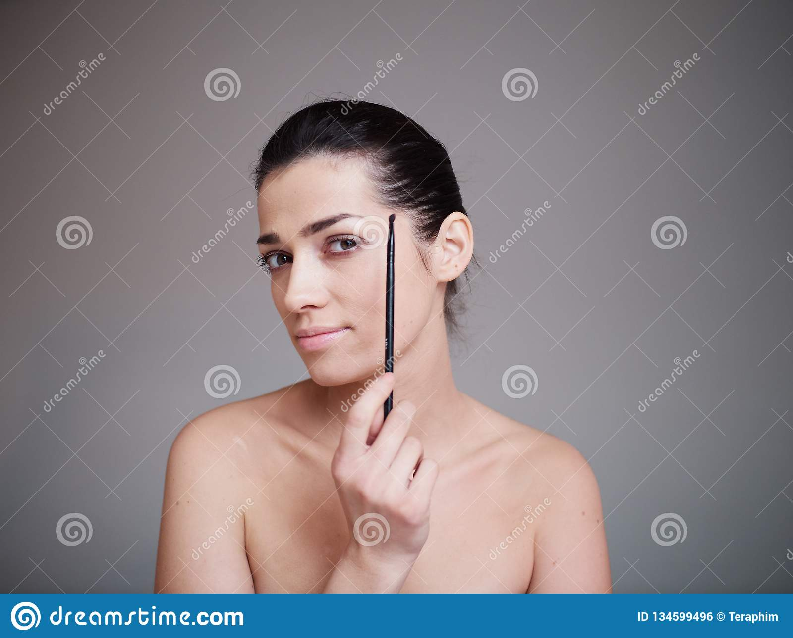 Beauty portrait of healthy female face with natural skin isolated on grey background. Make up concept