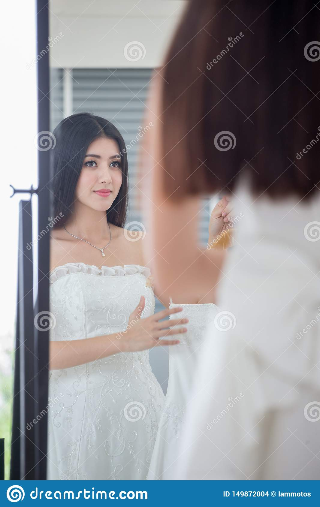 Beauty portrait of young asian bride is looking into the mirror and smiling while choosing wedding dress in wedding salon of