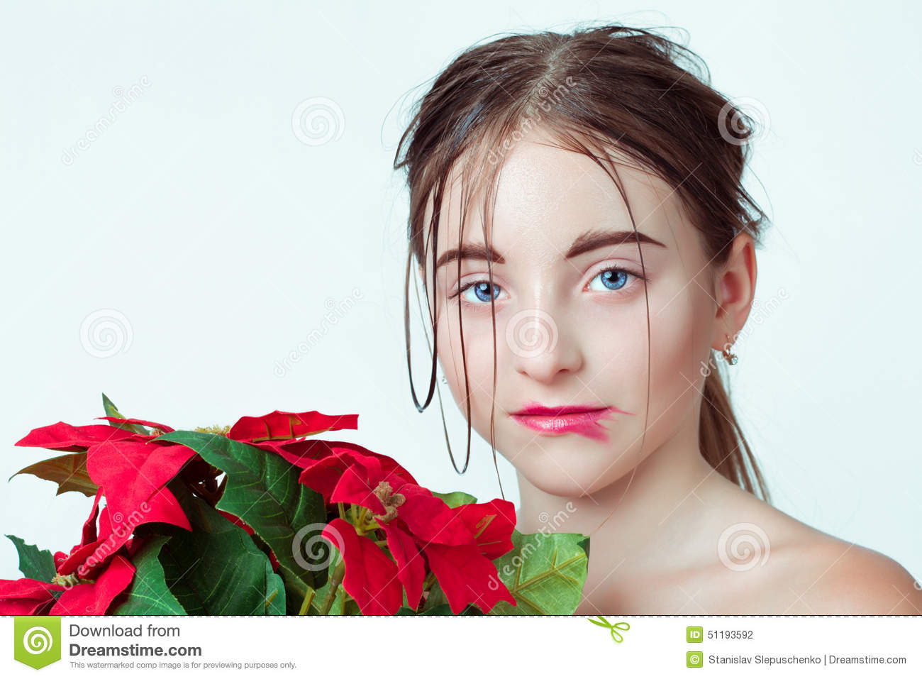 Beauty portrait of young girl. Morning image with the effect of wet face. The girl in the hands holding a red flower.